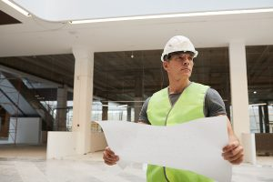 Large construction site manager looking at the drawings.