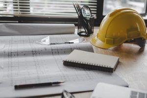Construction job blue prints, pen, and hardhat sitting on a desk.