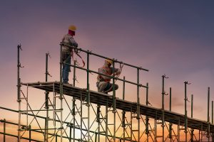 Men working on construction site with scaffold and building with sunset.