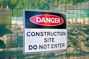 Danger Construction site do not enter sign on a fence surrounding the area.