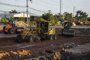 Large heavy equipment on a large construction site near a road.